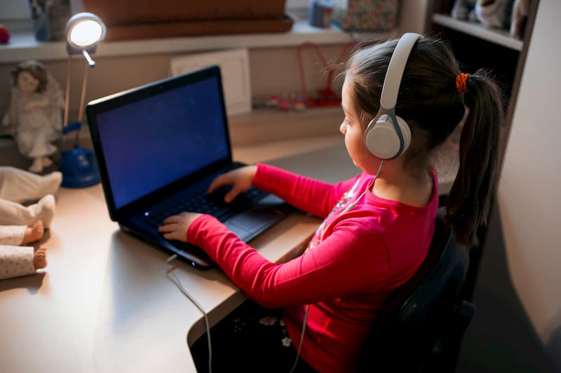 Dieťa sa vo svojej detskej izbe hrá na počítači a počúva hudbu