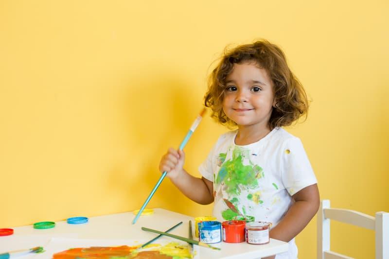 Dieťa v detskej izbe si maľuje obrázok