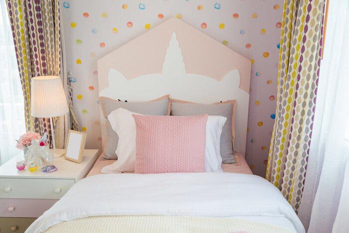 Obrázok interiéru dcérinej detskej izby s ružovo-bielymi vankúšmi a bielou prikrývkou na ružovej posteli so sladkými tapetami a závesmi a roletami.