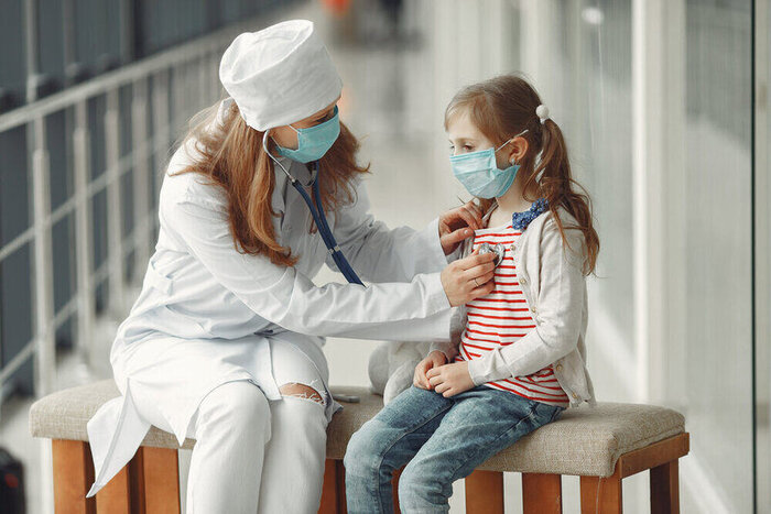 A doctor woman is examinating a child with stethoscope. They are wearing respirators.
