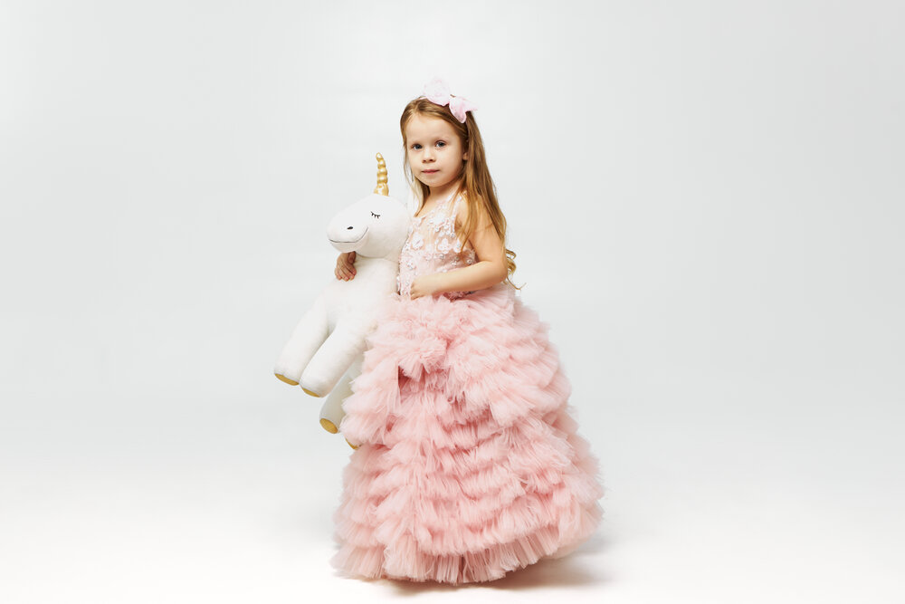 Adorable cute little girl dressed like princess in pink skirt posing isolated holding unicorn stuffed toy under her arm, looking at camera with broad happy smile. Childhood, joy and happiness