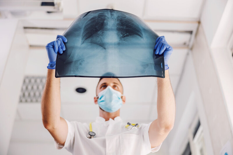 Doctor with face mask and rubber gloves looking at x-ray of lungs during corona virus.