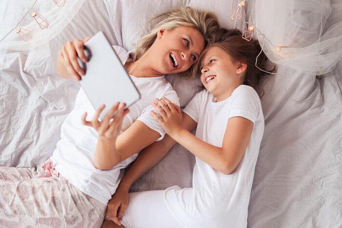 Rodina. Mama s dcérou v posteli pozerajú rozprávku na tablete.