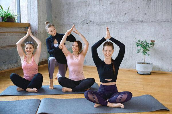 skupina troch dievčat cvičiacich jogu na podložkách