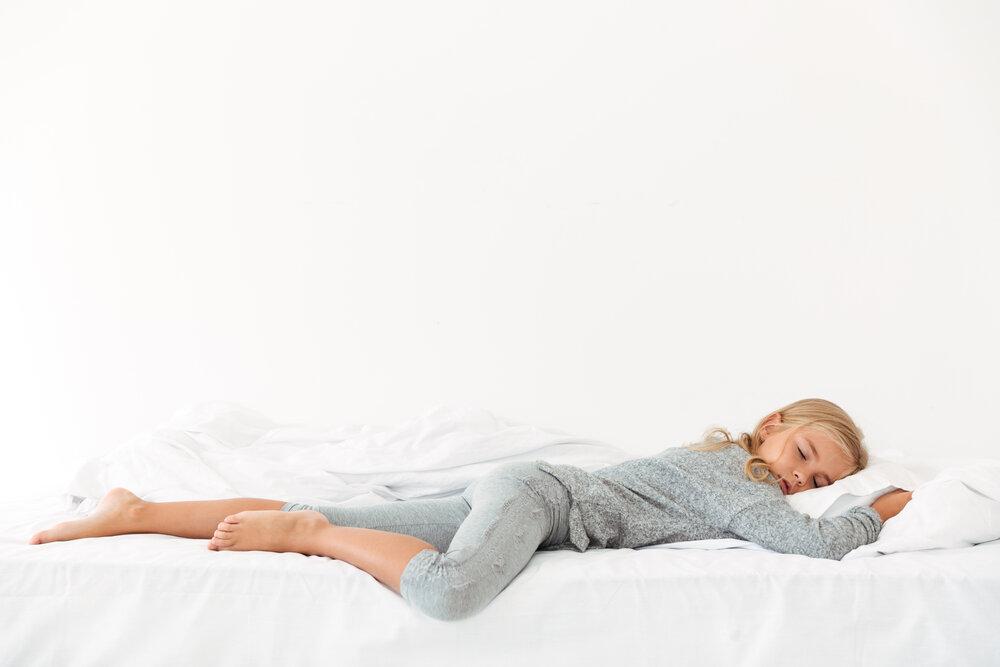 Po celej dĺžke portrét spiaceho dievčaťa v sivom pyžame ležiaceho v posteli