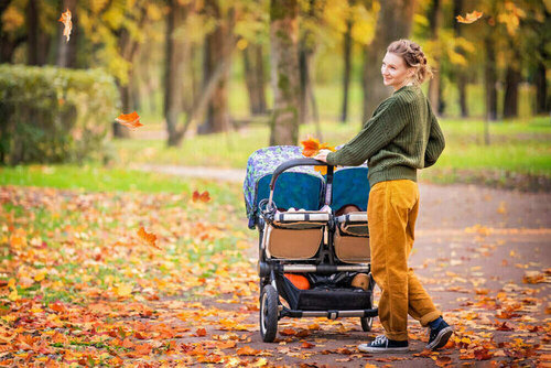 Happy mom are walking in the autumn park with a stroller for twins. Full-length portrait.
