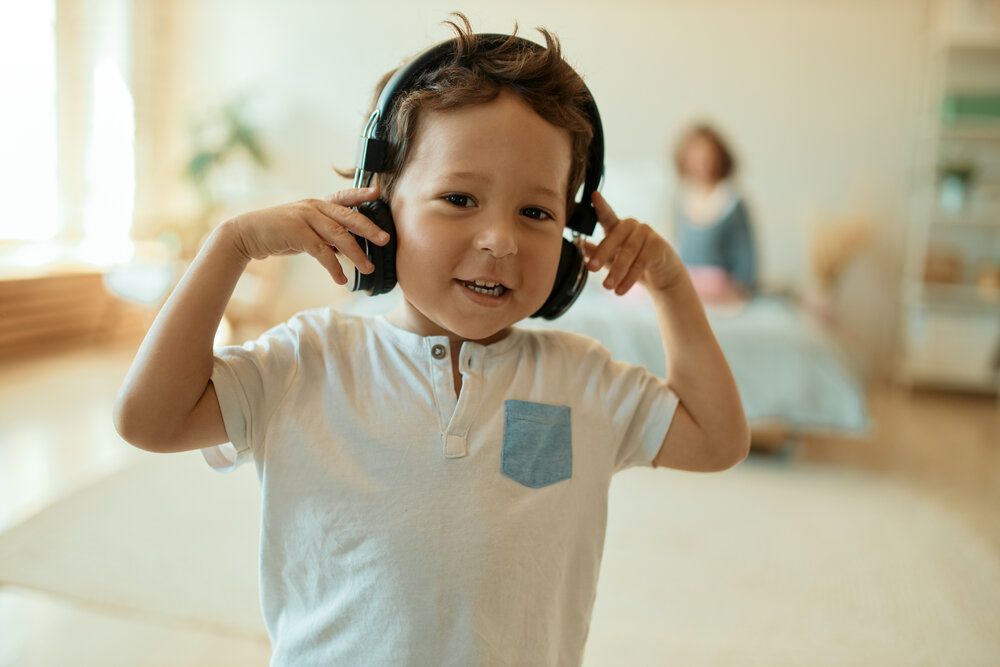 Indoor shot of adorable sweet mixed race little boy wearing wireless headphones, listening to music and dancing, his mother posing in background. Childhood, maternity, fun and technology concept