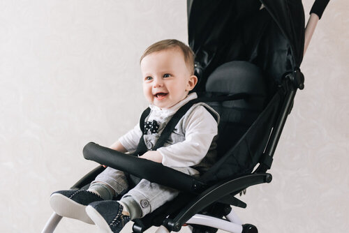 Little smiled boy sits in the baby buggy on the light background