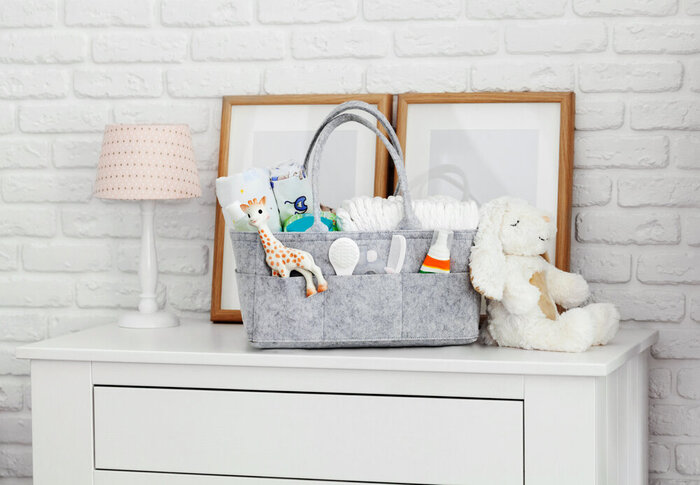 Mothers bag with toy, diapers and accessories on white background