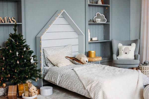 Drevená detská posteľ s vankúšmi a hračkami. Minimalistický vianočný dekor. Škandinávsky interiér