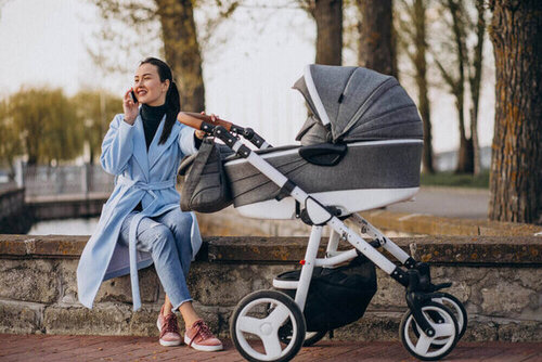 Young mother sitting with baby carriage in park