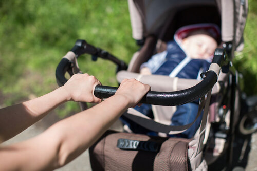 Young mother walking and pushing a stroller in the park
