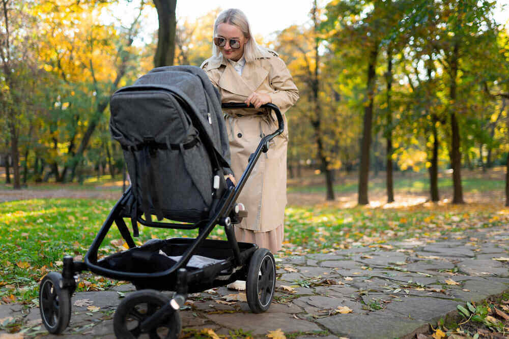 Mother with baby pram walking in autumn park