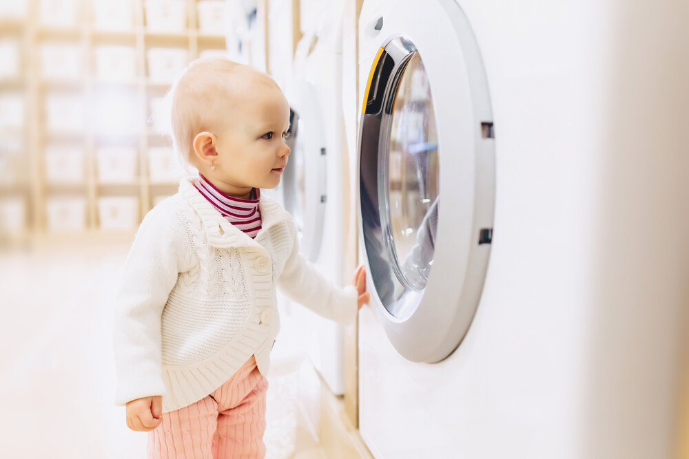 little baby girl playing ang looking at a washing machine