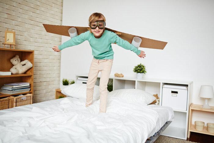 Dievča s ručne vyrobeným lietadlom za chrbtom stojace na posteli