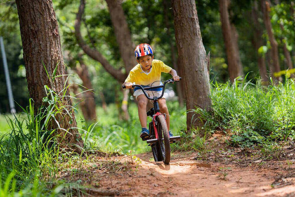 Asian boy is training for a happy mountain biking.