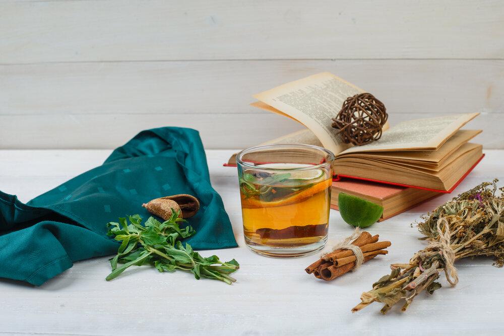 Detailný bylinkový čaj a kvety s knihami, citrónom, korením a zelenou šatkou na bielom pozadí.