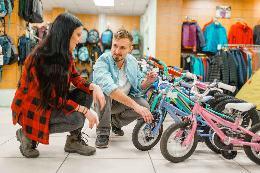 Couple choosing children's bicycle, shopping in sports shop. Summer season extreme lifestyle, active leisure store, customers buying cycle for family riding