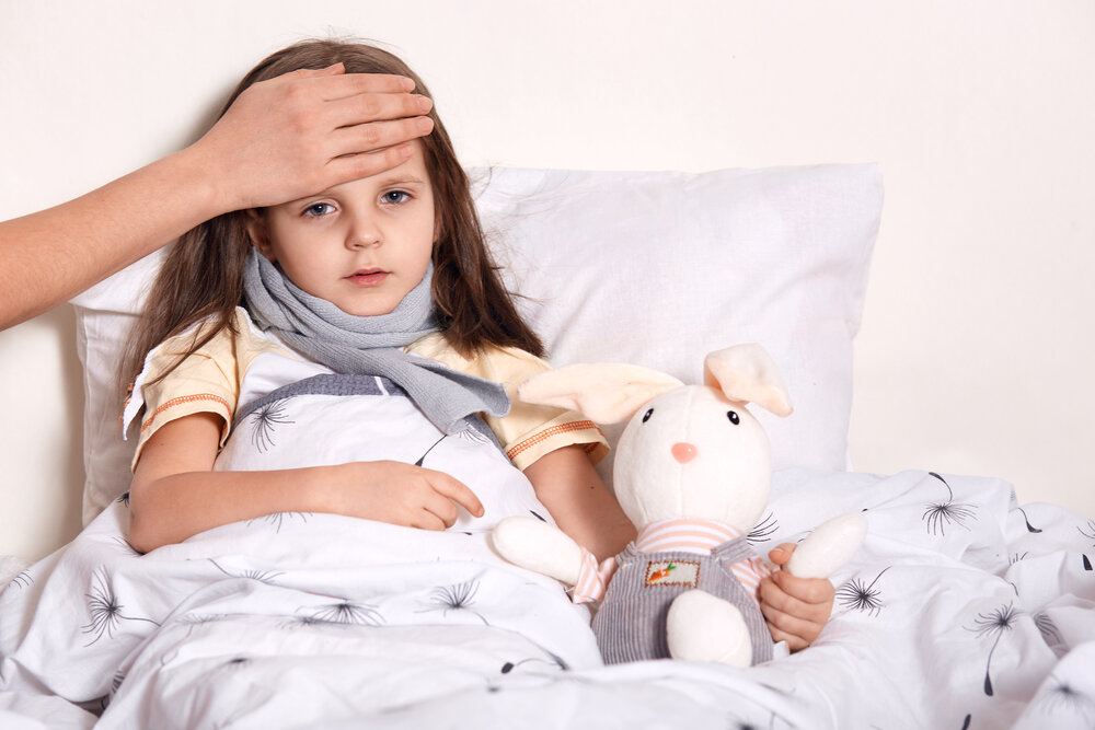 Indoor shot of little girl with fair hair lying in her bed, hugging favourite toy, having unknown hand on forehead, checking temperature, having scarf around neck, being on sick leave. Health concept.