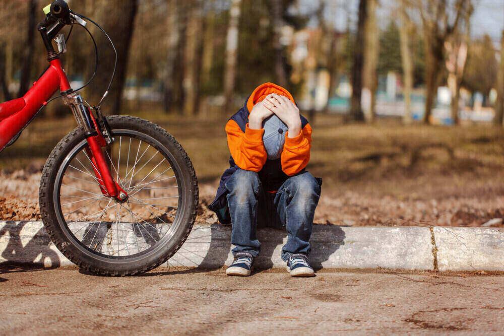 Sad child sitting near a broken bicycle.