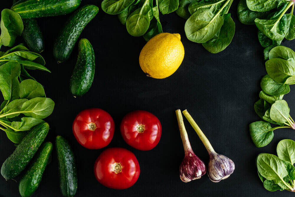 Various fresh vegetables organic food for healthy eating on dark background. Cucumbers Tomatoes Garlic Lemon Spinach. Top view.