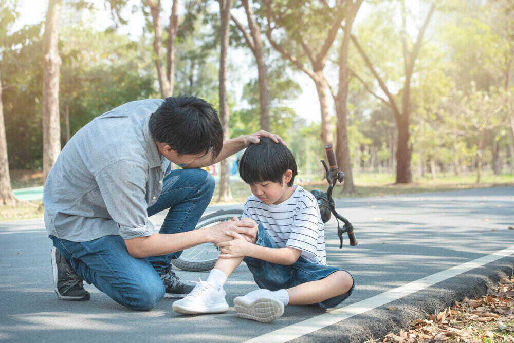 Young asian father of dad calms son that fell from the bike and he get injury on knee and leg while have weekend leisure in public park,accident can happen everywhere and every time.