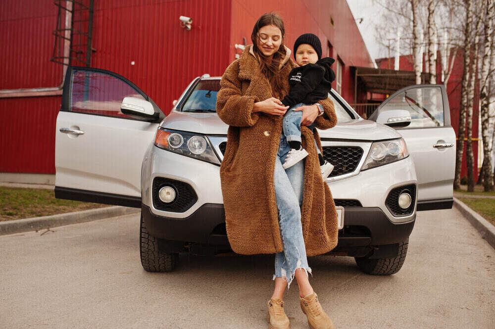Mladá matka a dieťa stoja neďaleko svojho suv auta. Koncept bezpečnej jazdy.