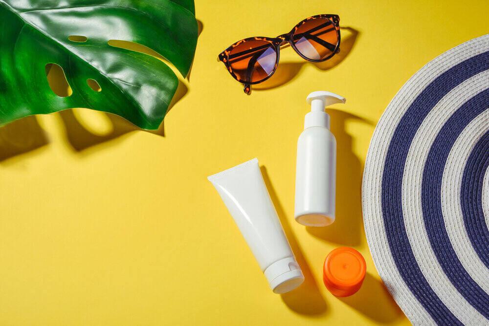 Objekty chrániace pred slnečným žiarením. Slamená dámska čiapka so slnečnými okuliarmi a ochranným krémom spf 30 zhora na žiarivo žltom pozadí. Plážové doplnky. Koncept letnej cestovateľskej dovolenky.