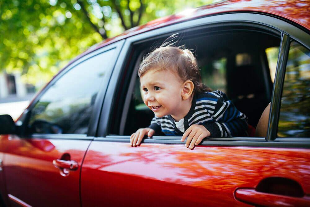 Chlapček v aute si užíva jazdu pri otvorenom okne