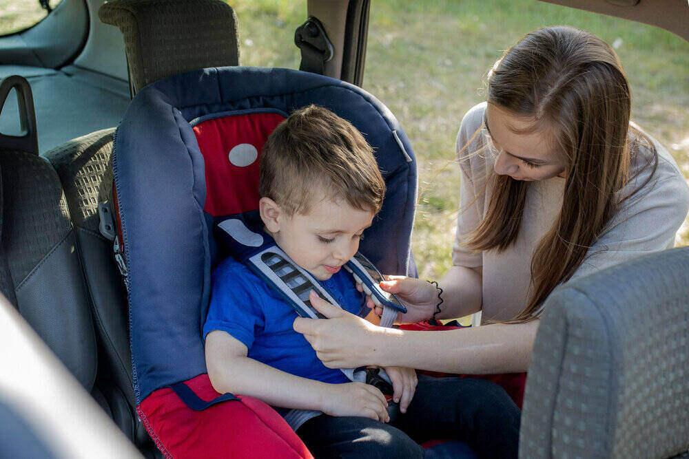 Šťastná matka pozerá na svojho syna v detskej sedačke. Mladá žena pripravuje dieťa na výlet. Koncept bezpečnej jazdy.