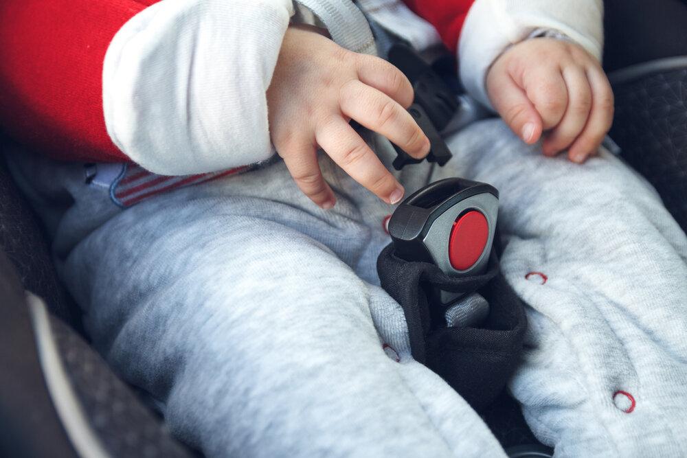 Dieťa si skúša zapínať bezpečnostný pás v autosedačke