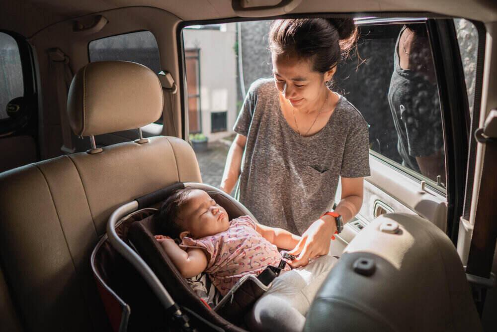 ázijská matka upevňuje pred jazdou detskú sedačku v aute