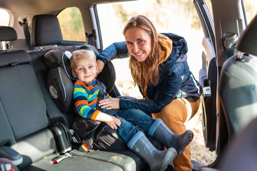 Matka upevňujúci bezpečnostný pás pre svojho chlapčeka v jeho autosedačke. Bezpečnosť detských autosedačiek.