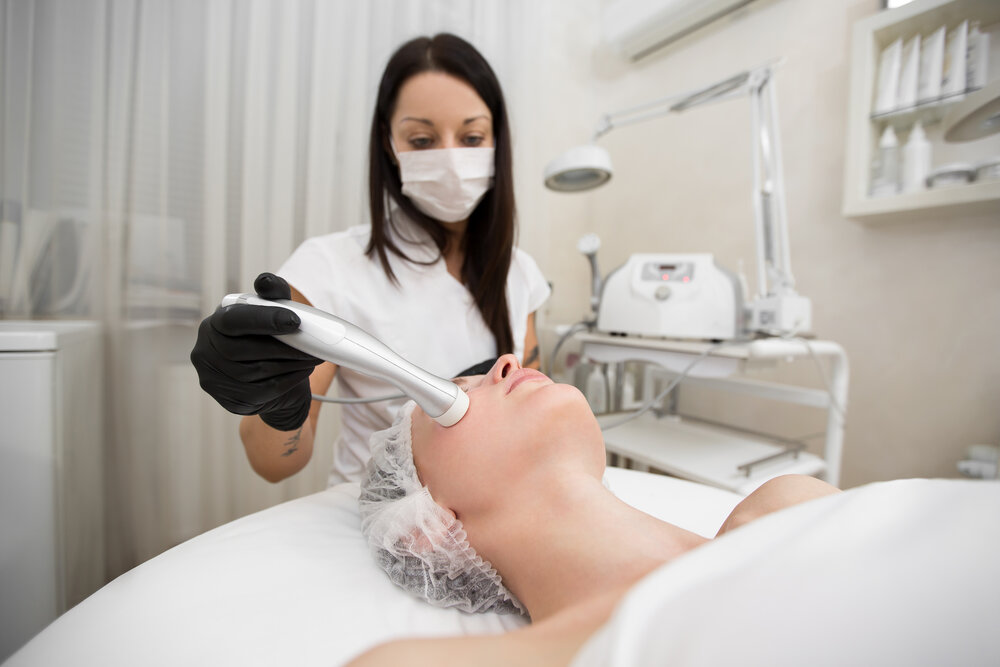 Pohľad zhora na procedúru neinjekčnej mezoterapie pre mladé dievča v kúpeľnom salóne. Kozmetička robí moderné trendy proti starnutiu