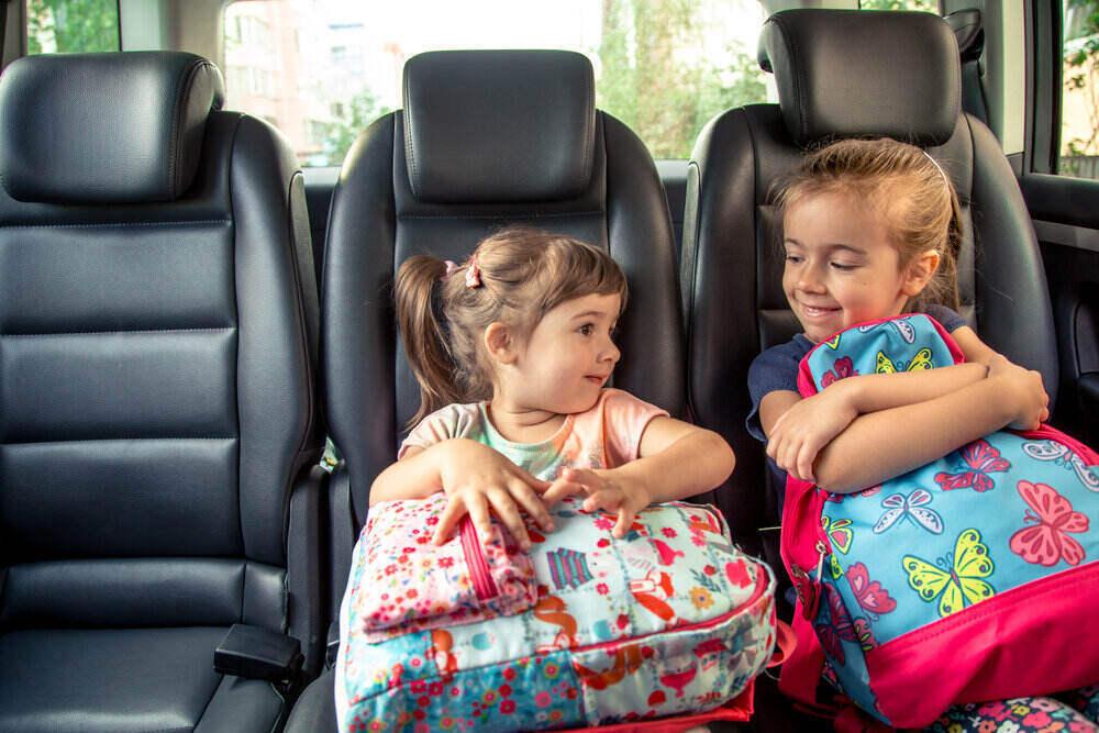 Deti v aute chodia do školy, šťastné, milé tváričky sestier, žiaci materskej školy so školskými batohmi, sedia v rodičovskom aute