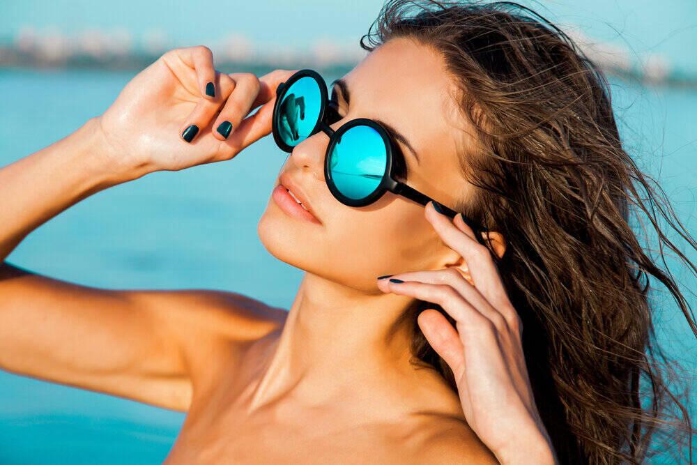 portrétnej štýlovej krásnej sexy dievčiny v okuliaroch s mokrými vlasmi na slnečnej pláži s modrou vodou