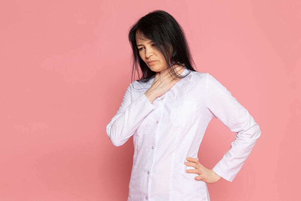 Dámu v bielej košeli sprevádza bolesť hrdla