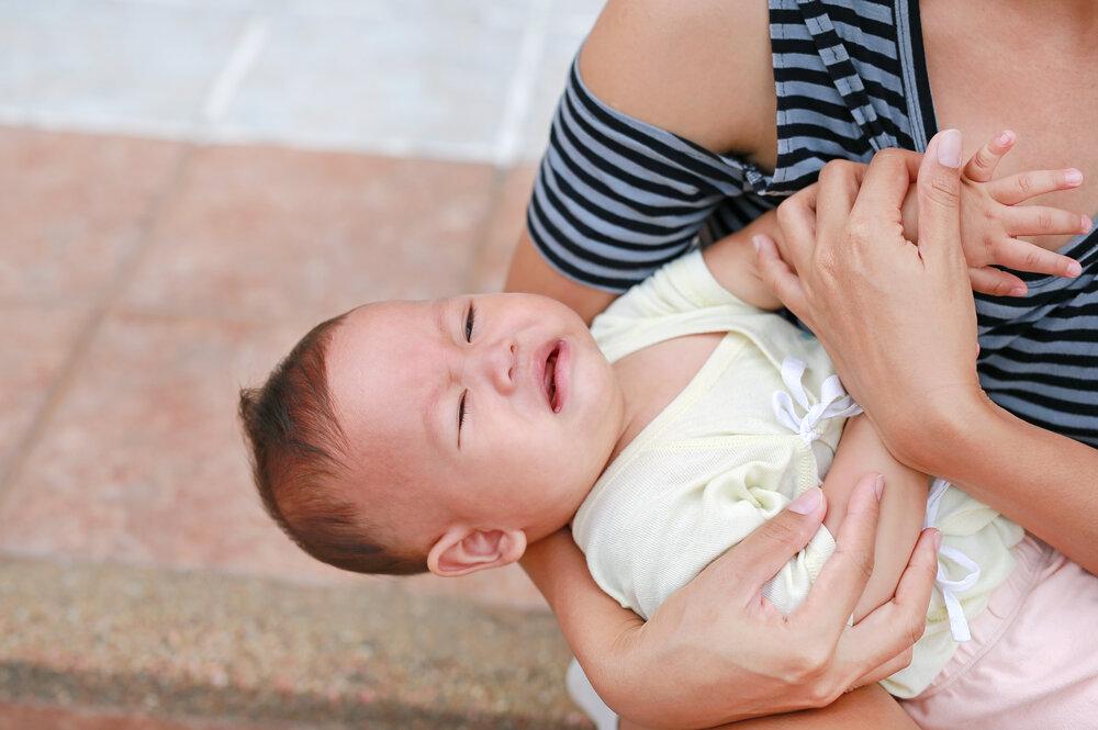 Ázijská matka drží kričiaceho novorodenca