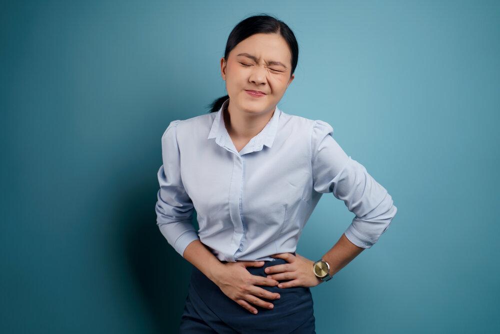 Ázijská žena trpiaca bolesťou žalúdka.