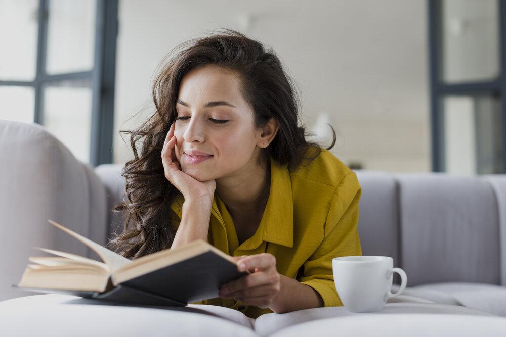 spokojná žena si číta knihu a popíja kávu