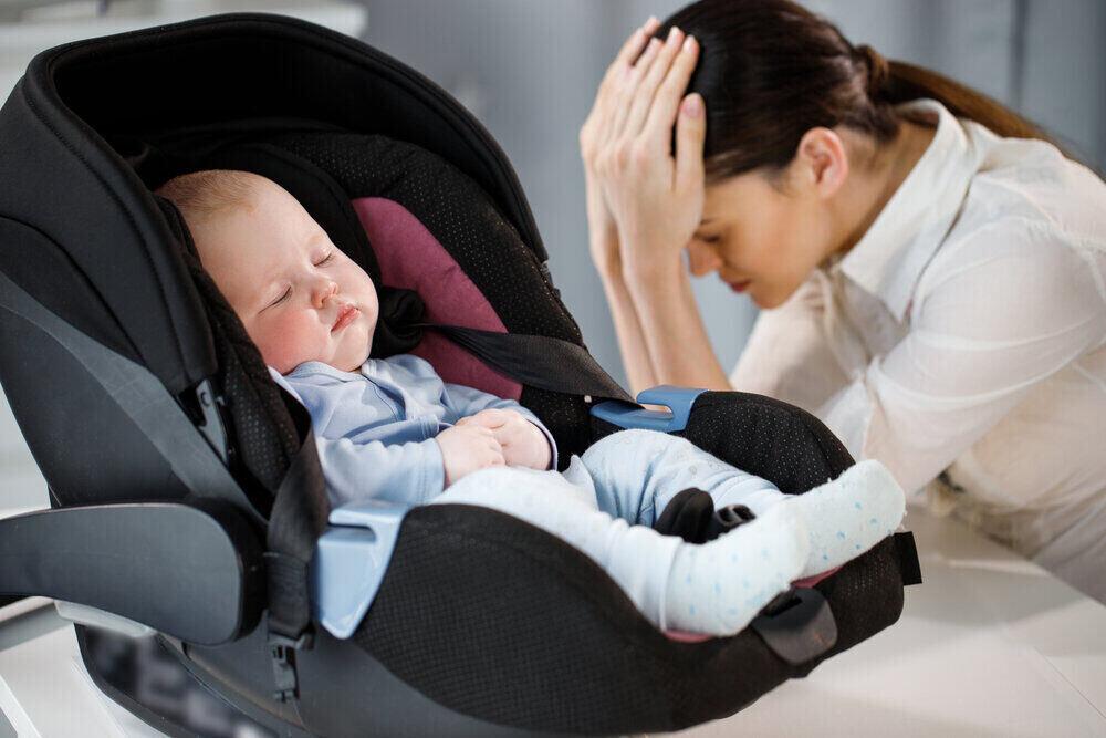 Unavená matka je smutná blízko spiaceho dieťaťa