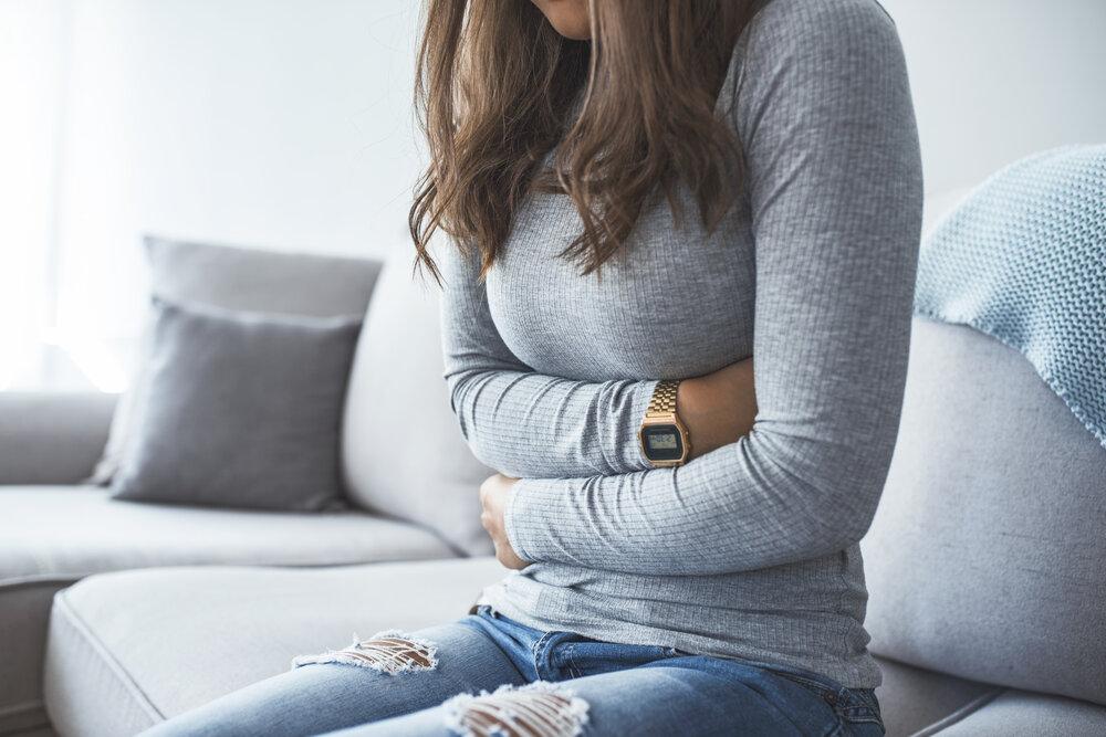 Krásna mladá žena sedí na posteli a drží si ruky na bruchu. Žena s bolesťami brucha.