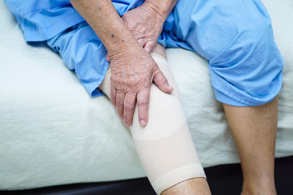 Pacientka má poranené a obviazané koleno.