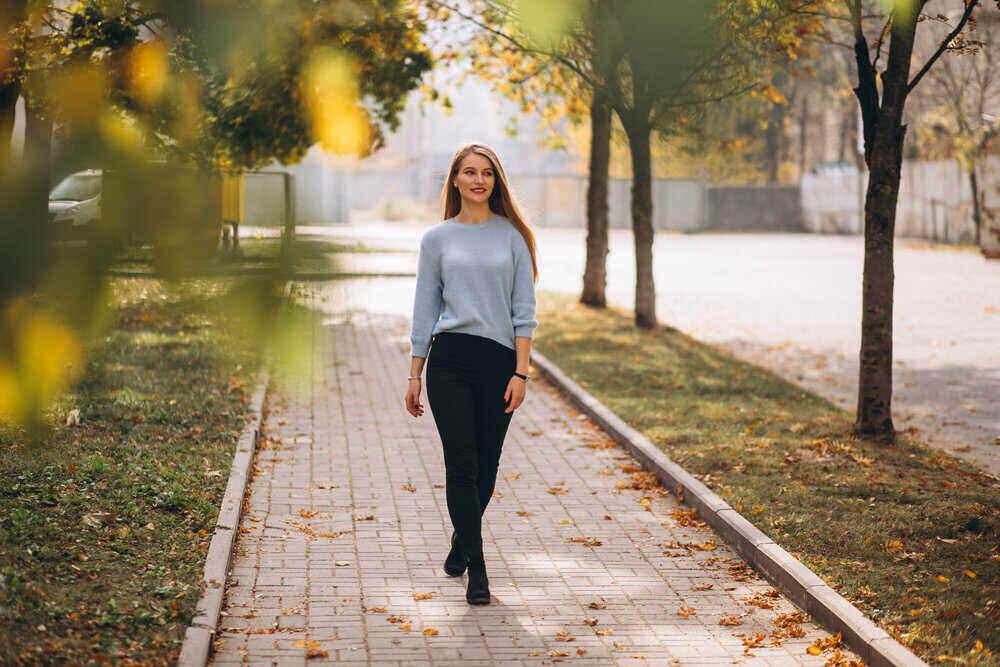 Mladá žena v modrom svetri sa prechádza v jesennom parku