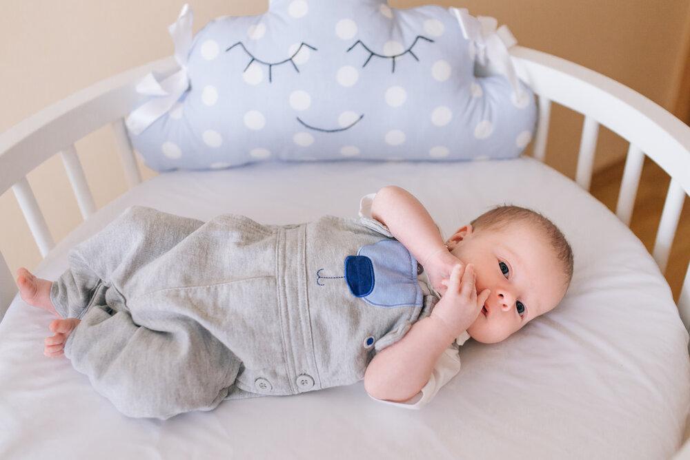 Krásne novonarodené dieťa ležiace v okrúhlej postieľke v jemných sivých, modrých a bielych tónoch