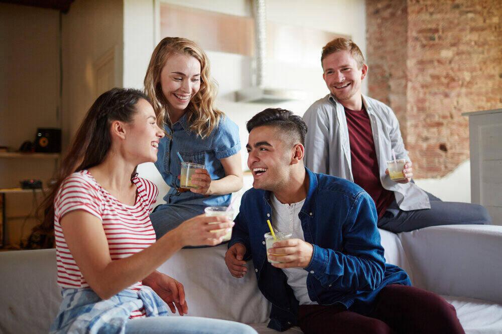 Mladí veselí spoločníci bez stresu, ktorí pri domácom večierku diskutujú o zábavných veciach.