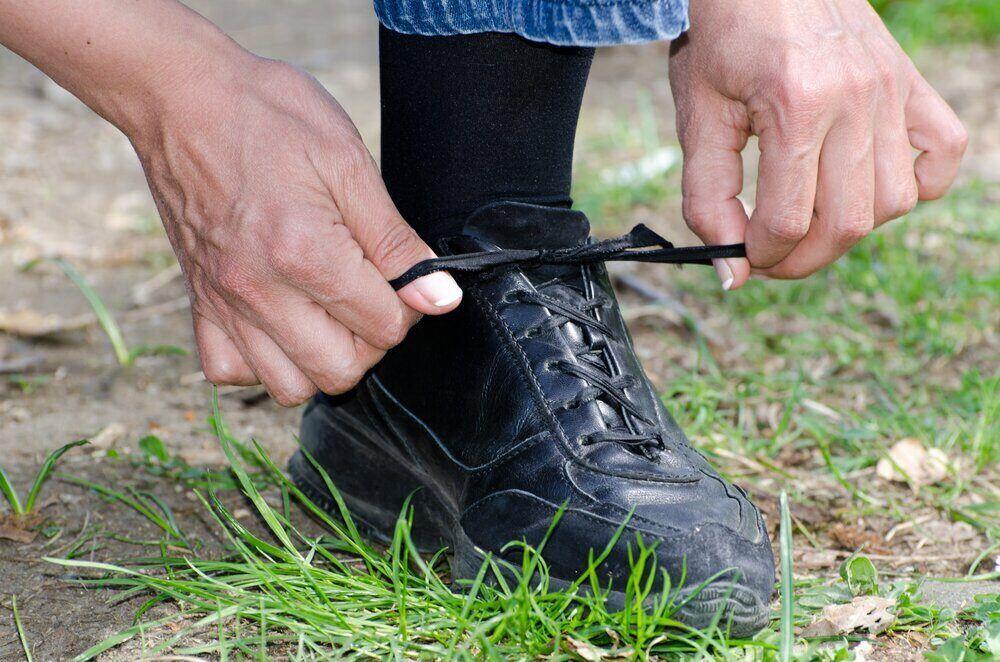 Detailný záber muža, ktorý si zaviazal šnúrku na zemi, koncept pevnej obuvi
