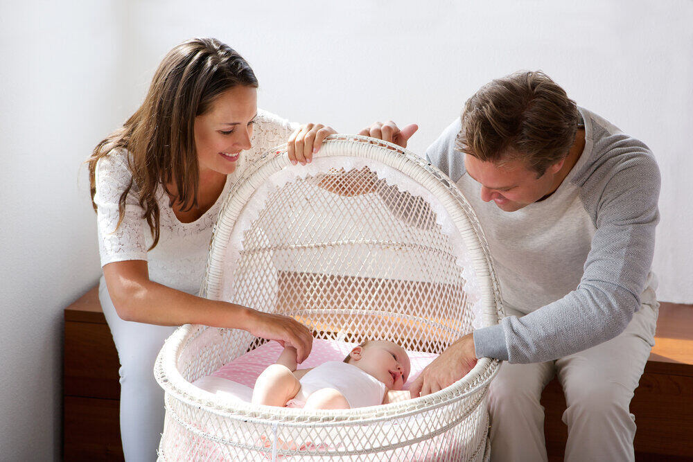 Šťastný pár sa usmieva na svoje dieťa v postieľke