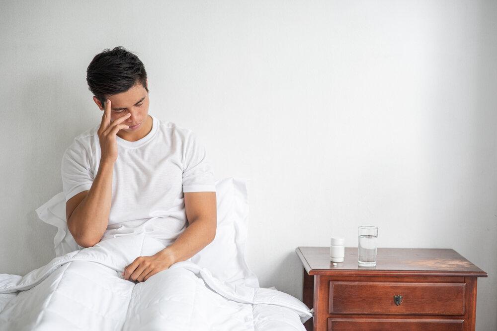 Chorý muž sedí na posteli a rukou sa dotýka hlavy.