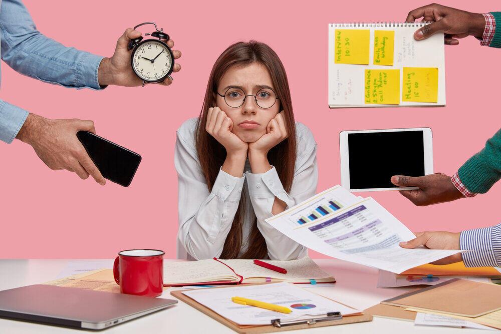Smutná zaneprázdnená žena si drží ruky pod bradou. Projektové práce, papiere, neznámi ľudia naťahujú ruky s poznámkami, budíkom, smartfónom